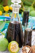 stock photo of walnut  - Walnut liqueur with green walnuts - JPG