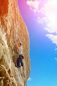 foto of climbing wall  - Young man climbs on a rocky wall - JPG