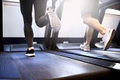 image of treadmill  - Toned Legs of Healthy Young Couple Exercising on Treadmill Device Inside Fitness Gym - JPG