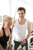 image of rep  - Good Looking Fitness Instructor Smiling at Camera While Assisting a Young Woman Exercising on Pulley Device Inside the Gym - JPG