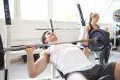 Постер, плакат: Man Lifting Barbell Weight In Brightly Lit Gym