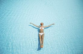 pic of floating  - View of the young woman floating in the pool - JPG
