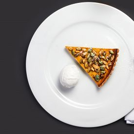 pic of pumpkin pie  - Pumpkin Pie with whipped cream and pumpkin seeds on white plate over black chalk board - JPG