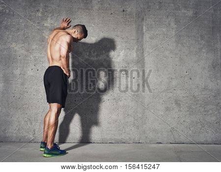 poster of Young man resting after an active fitness training while standing against gray wall with copy space area for your text message satisfied fit male man resting after an active fitness training