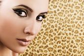 foto of makeup artist  - Portrait of woman with artistic makeup on leopard patterned background - JPG