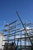 picture of cherry-picker  - Cherry picker and crane beside metal frame of new building - JPG