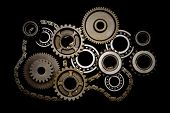 Set of gears, ball-bearings and chain isolated on black background