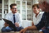 Senior couple planning their investments with financial advisor in living room poster