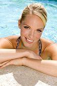 stock photo of summer fun  - Beautiful young woman at a pool - JPG