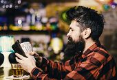 Guy Spend Leisure In Bar, Defocused Background. Hipster Holds Wallet, Counting Money To Buy Drinks.  poster