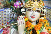 stock photo of krishna  - Statue of garlanded Hindu god Krishna playing flute in Delhi - JPG