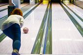 Young Woman Throwing Ball In Bowling Club. Young Woman Playing Bowling. Copy Space. Woman In Club Fo poster