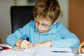 Cute Little Kid Boy With Glasses At Home Making Homework, Writing Letters And Doing Maths With Color poster