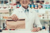 Closeup Pharmacist Holding Brown Bag With Medicine. Close Up Of Smiling Mature Woman Pharmacist Wear poster
