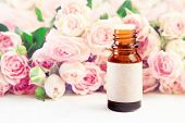 Glass Bottle Of Essential Oil With Empty Craft Label On Table With Roses Pink Soft Blurred Backgroun poster