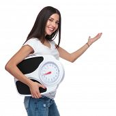 side view of casual woman holding a scale and presenting to side while standing on white background poster