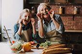 Grandma And Granddaughter Having Fun In Kitchen. Grandma And Granddaughter Cooking Food. Vegetable S poster