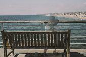 Girl Fading Into The Background Sitting On A Bench Looking At The Ocean poster