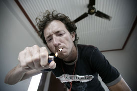 pic of marlboro  - Young man lighting up a cigarette in hotel room - JPG