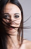 picture of windswept  - Closeup portrait of a beautiful brunette with face covered by windswept hair - JPG