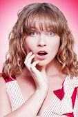 picture of jaw drop  - Woman looking shocked and appalled with a dropped jaw and wide eyes as she stares straight into the lens on a pink studio background with colour gradient - JPG