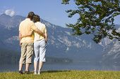 foto of love couple  - Couple contemplating arm in arm a mountain lake - JPG