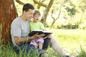 stock photo of adolescent  - young father with his little daughter reads the Bible - JPG