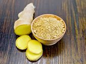 pic of fruit bowl  - Ginger powder in a wooden bowl and sliced ginger root on a dark wooden board - JPG