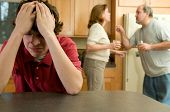 stock photo of drama  - Parents drinking and arguing behind teenage son  - JPG