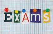 picture of line graph  - The word Exams in cut out magazine letters pinned to blue lined graph paper background - JPG