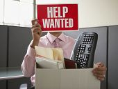 Businessman holding up help wanted sign