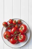 Vine tomatoes in rustic enamel bowl over white timber.  Lots of copy space.