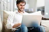 stock photo of comforter  - Young man relaxing on the sofa with a laptop - JPG