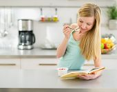 Happy Teenager Girl Reading Book And Eating Yogurt In Kitchen