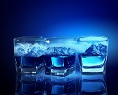 Three glasses of blue liquid with mountain illustration in
