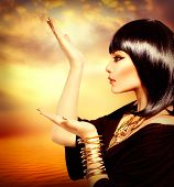 Egyptian Style Woman with Magic Light in Her Hand. Golden Jewels. Egypt Styled Makeup. Gold Light. J
