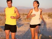 Fitness sport couple running jogging outside laughing happy training together outdoors. Runners in c