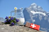 Swiss chocolate and jug of milk against mountain peak. Switzerland