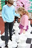 Boy and girl move big chess pieces on big chessboard in park.