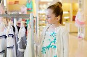 Little girl stands, looking upon dresses hanging on stand in clothing store