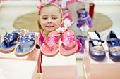 stock photo of shoe-box  - Little girl looks up on toeless shoes that stands on top of shoe boxes - JPG