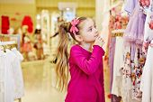 Little girl looks with interest, touching chin with fingers, upon dresses hanging at stand in clothi
