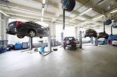 Four cars on lifts and on floor in small service station. Cars prepared to diagnosis and repair.