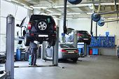 stock photo of motor vehicles  - Three black cars stand in small service station and two men repair one car - JPG