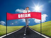 Smiling young businessman running on a road with a banner with dream written on it