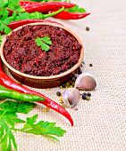 image of fenugreek  - Tabasco adjika in a clay cup different hot peppers garlic parsley fenugreek on the background of sack cloth - JPG