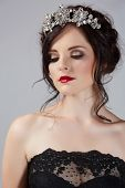 foto of gothic hair  - Beautiful brunette young bride with braided hair with shiny crown wearing black lace dress in studio - JPG