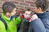 stock photo of stop bully  - Big bullies taking on small boy after school - JPG