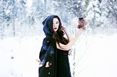 image of witch ball  - Witch or woman in black cloak with fire ball in white snow forest - JPG