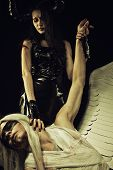 image of hells angels  - Horned girl in black latex clothes posing with wounded one - JPG
